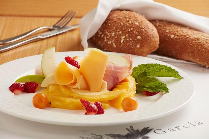 Desayuno frugal de la casa con conitos de jamón ahumado, jamón de pavo, queso holandés, mozzarella y frutas mixtas.