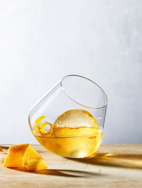 Lifestly image of whisky glass with ice on a wooden surface lit by bright daylight for Waitrose By Ian Oliver Walsh Still Life Photographer London