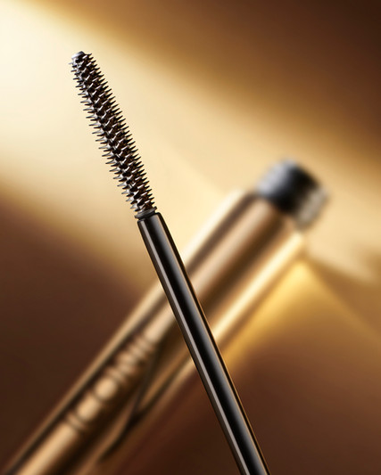 Macro close up shot of a mascara brush with a strong depth of field agains a glowing gold background with a shard of dynamic light By Ian Oliver Walsh Still Life Photographer London