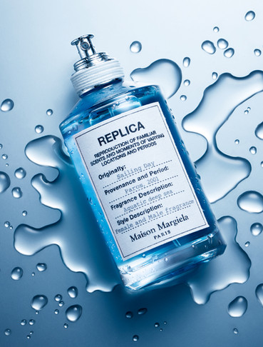 Designer Maison Margiela fragrance perfume lays on a pool of splashed liquid or water against a cool blue background By Ian Oliver Walsh Still Life Photographer London