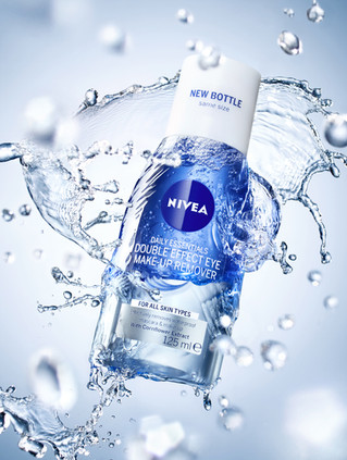 Nivea makeup skin cleanser product flying through the air as high speed water splashes in to it forming droplets and ripples By Ian Oliver Walsh Still Life Photographer London