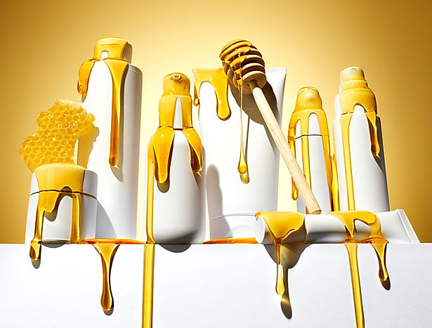 Heroic beauty and cosmetic products photographed on a white plinth with pours and drips of golden liquid honey as sunlight casts hard shadows on them by still life photographer Ian Oliver Walsh Lonodon