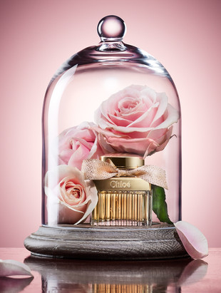 Chloe fragrance perfume inside a bell jar for flowers and roses upon a wooden table as an editorial for LOOK magazine By Ian Oliver Walsh Still Life Photographer London