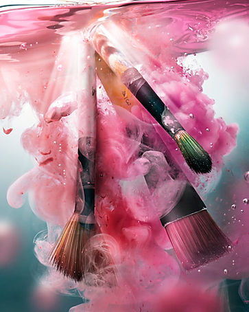 Brushes splashing in to water creating ripples and swirls of paint and bubbles Heroic beauty and cosmetic products photographed on a white plinth with pours and drips of golden honey as sunlight casts hard shadows on them by still life photographer Ian Oliver Walsh Lonodon
