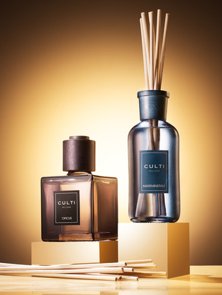 Fragrance home reed diffuser products sit on golden plinths as warm glowing light shines through them for Space NK China By Ian Oliver Walsh Still Life Photographer London