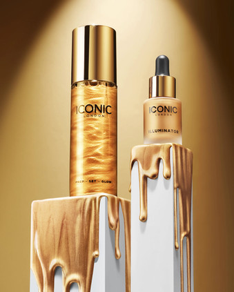 moving image of iconic gold beauty and make-up products on plinths with shimmering gold liquid dripping down as swirls of sparkling water loop in the bottle by Ian Oliver Walsh Still Life Photographer