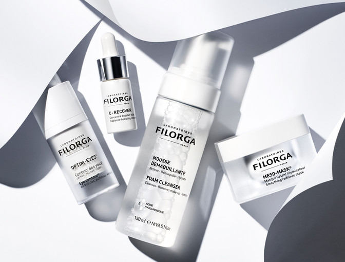 Filorga skincare serums and cosmetic products lay on a minimal monochrome background as swirls of papert art surround them By Ian Oliver Walsh Still Life Photographer London