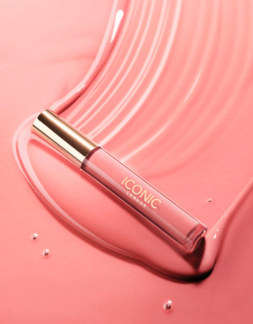 Iconic lipgloss sweeps across a large pool of product leaving a dynamic texture of gloss on a bright pink background By Ian Oliver Walsh Still Life Photographer London