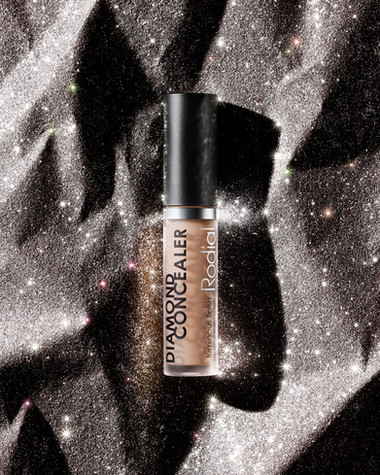 A Rodial beauty concealer product lays on a formation of sparkling diamond rock, lit with hard deep shadows By Ian Oliver Walsh Still Life Photographer London