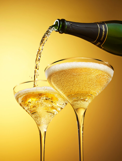 Sparkling champagne pouring in to a glass from a bottle showing bubbles and fizz against a golden background for waitrose drinks By Ian Oliver Walsh Still Life Photographer London