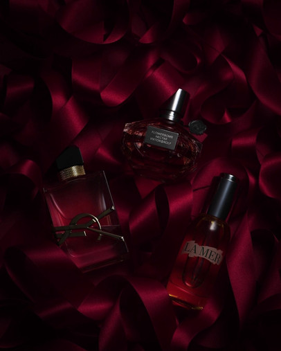 video of YSL and luxury designer perfumes and fragrances sit on a bed of red ribbon giving the feeling of romance and gifting By Ian Oliver Walsh Still Life Photographer London