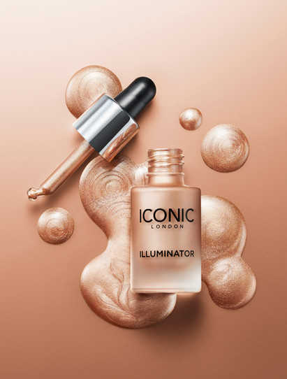 Advertsing iconic London makeup illuminator as it rests in a shimmering pool of its liquid with droplets surrounding By Ian Oliver Walsh Still Life Photographer London