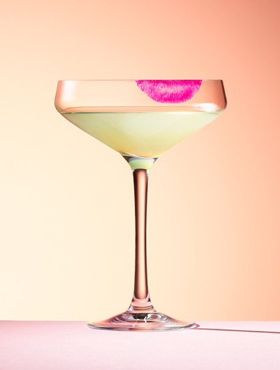 alcohol cocktail glass left with pink splistick stain on a sunset background By Ian Oliver Walsh Still Life Photographer London