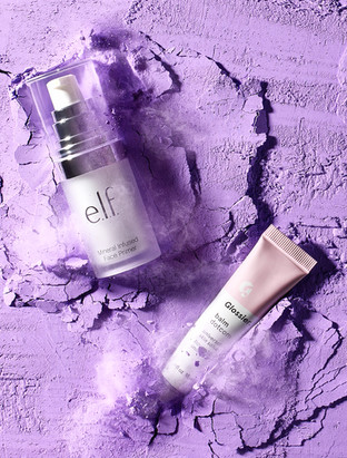 ELF and Glossier beauty products dynamically crashing in to a bed of purple makeup powder captured at high speed creating textues andclouds of smoke By Ian Oliver Walsh Still Life Photographer London