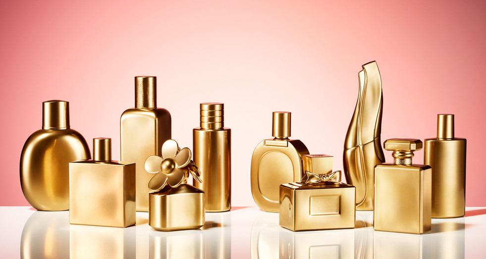 designer luxury perfume, fragrance and after shave bottles in solid gold on a reflective surface for cosmopolitan magazine By Ian Oliver Walsh Still Life Photographer London