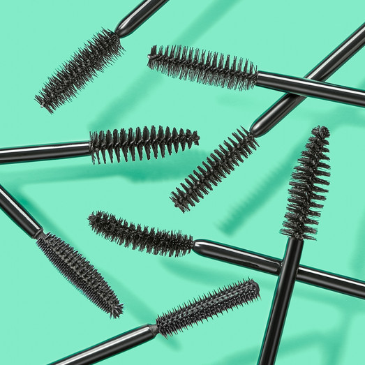 Multiple black mascara brushes close up and playfully arranged against a bright green for Boots retail By Ian Oliver Walsh Still Life Photographer London