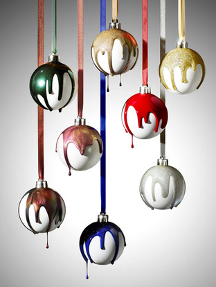 festive baubles hang by ribbon as sparkly and shimmering nail polish pours over them and drips By Ian Oliver Walsh Still Life Photographer London
