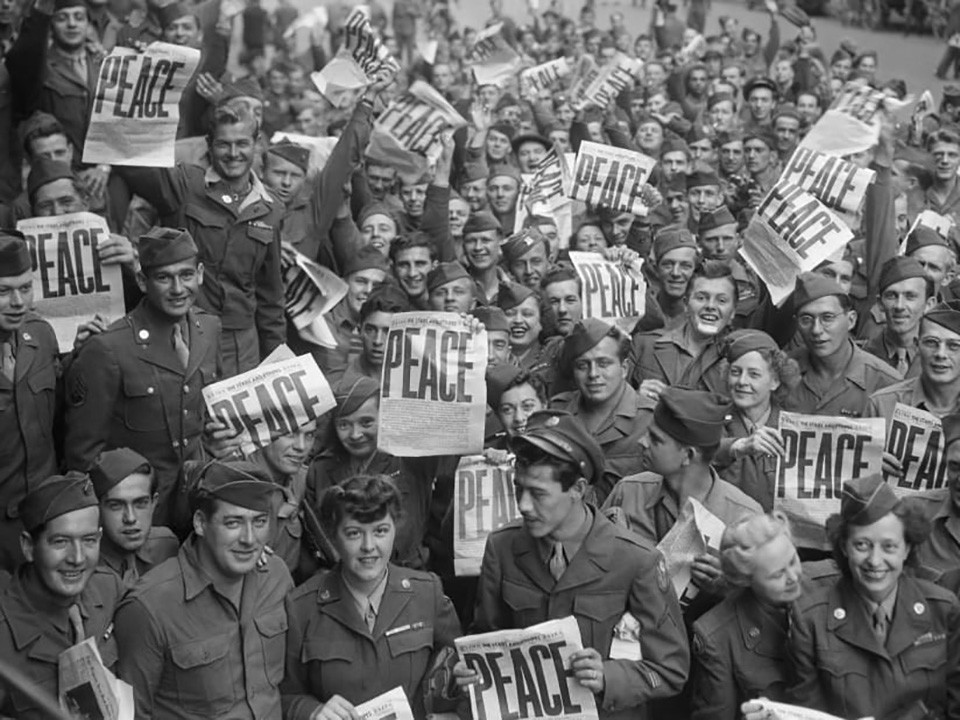 Soldiers holding newspapers with the word PEACE written in big bold letters.