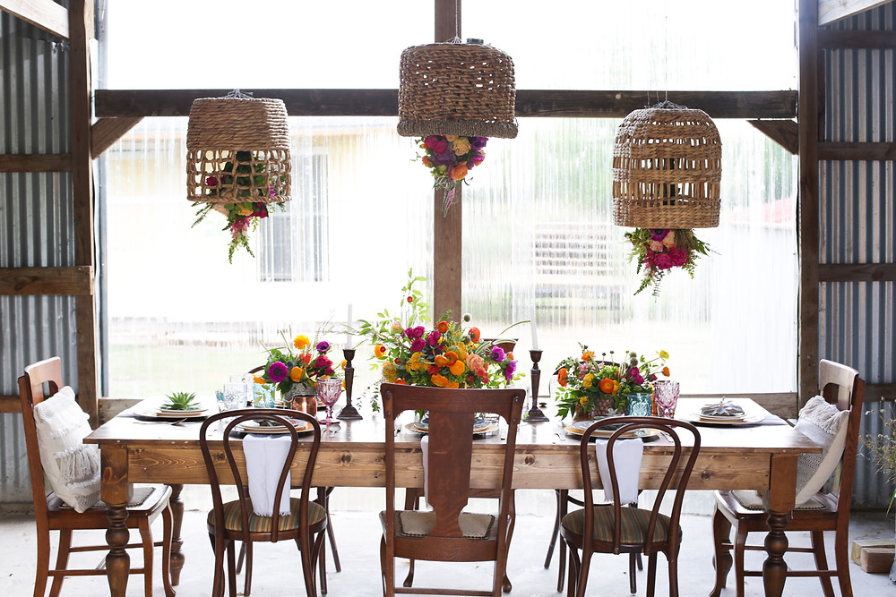 Woven Boho Baskets hung with floral bouquets over farmhouse reception table