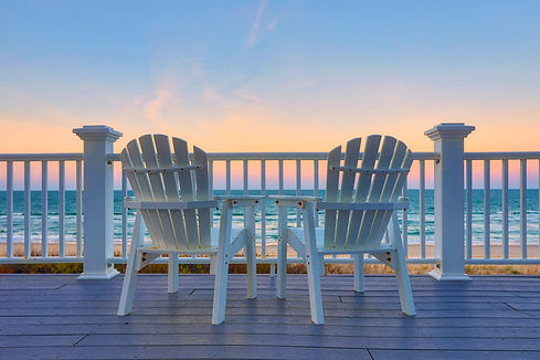 Empty Adirondack chair on a deck balcony overlooking the beach and the ocean at sunset.jpg
