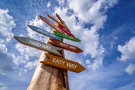 Crossroad signpost saying Hard Way , Eas
