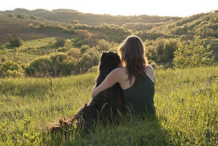 A beautiful young woman hugs her dog as they sit in a field.jpg