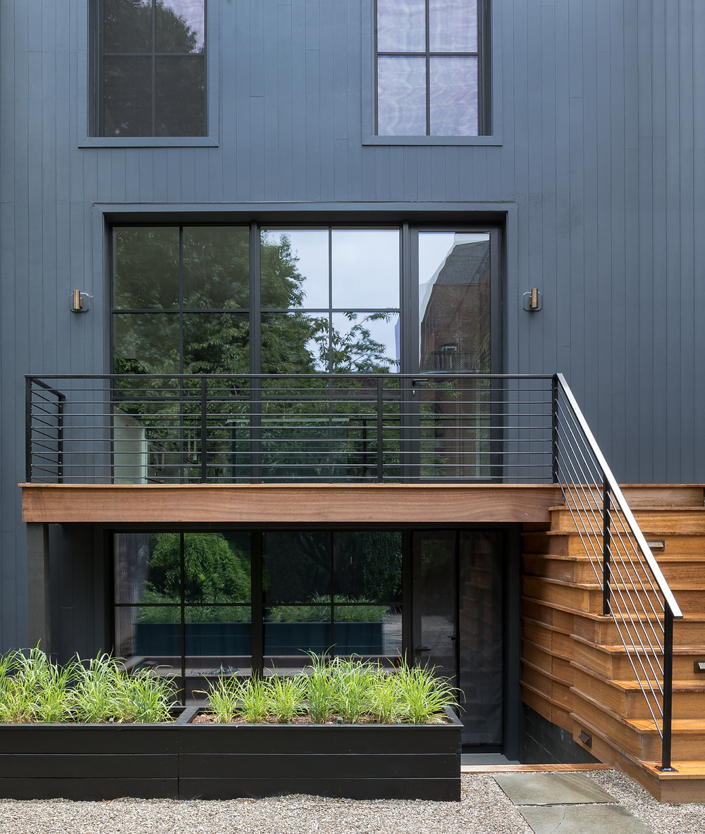 Modern steel railings complement the new steel windows on the back wall, which continue down to the garden level (that space was converted into a separate apartment for the homeowners' parents or a future rental). The architects used Boral'sTruexterior vertical siding with a nickel gap joint for the exterior cladding and mahogany wood for the new deck.