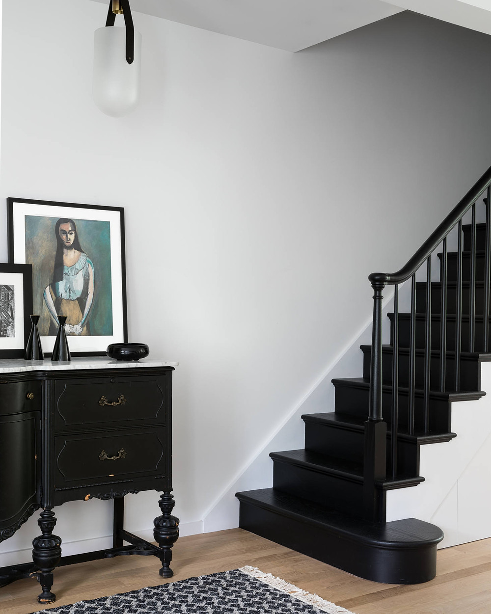 The architects freshened up the whole home with a coat of Benjamin Moore Decorator's White and painted the entry staircase a glossy black for contrast. The light fixture is Allied Maker's Well Pendant.