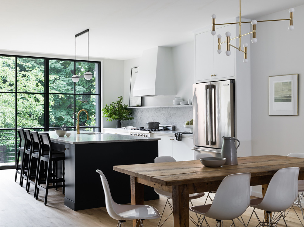 The open kitchen and dining area are flooded with light from the new glass wall that leads to the rear yard. The fixture over the dining table is Atomium from Lambert & Fils.
