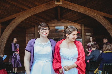 Queer femme couple leaves ceremony.
