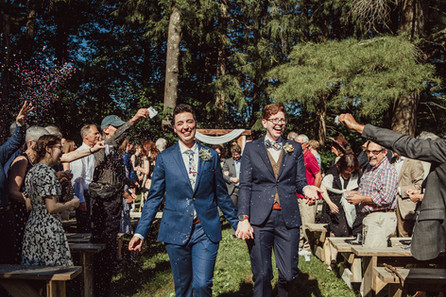Couple leaves wedding as family throws confetti.