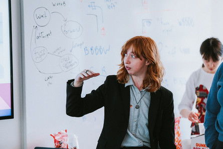 Redhead student stands infront of a whiteboard as she talks about the design process.