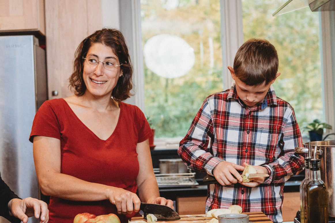 Dani smiles off to the side as her son focuses on cooking.
