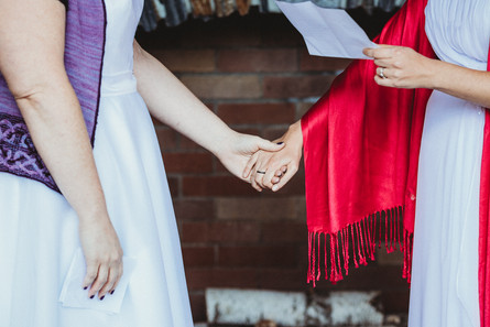 Lesbian couple holds hands, their knit shawl hang down.
