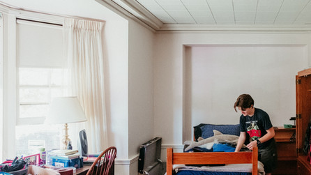 Student moving into a dorm that was once a large common room.