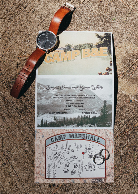 Wedding invite laid out with the wedding rings and watch.