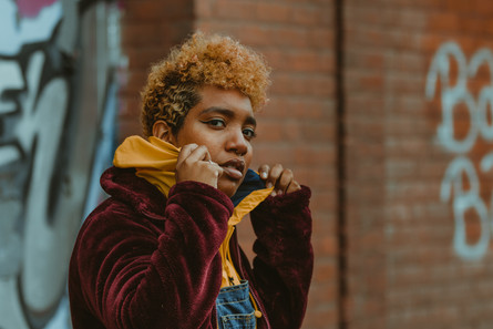 Portrait of Meliq (they/them) popping their collar in front of a brick wall