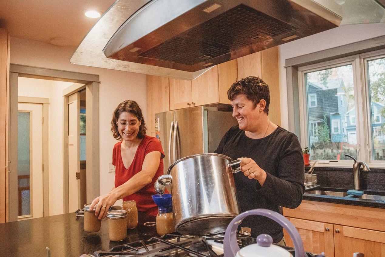 Lesbian couple, Dani and Denise finish canning apple sauce jars.