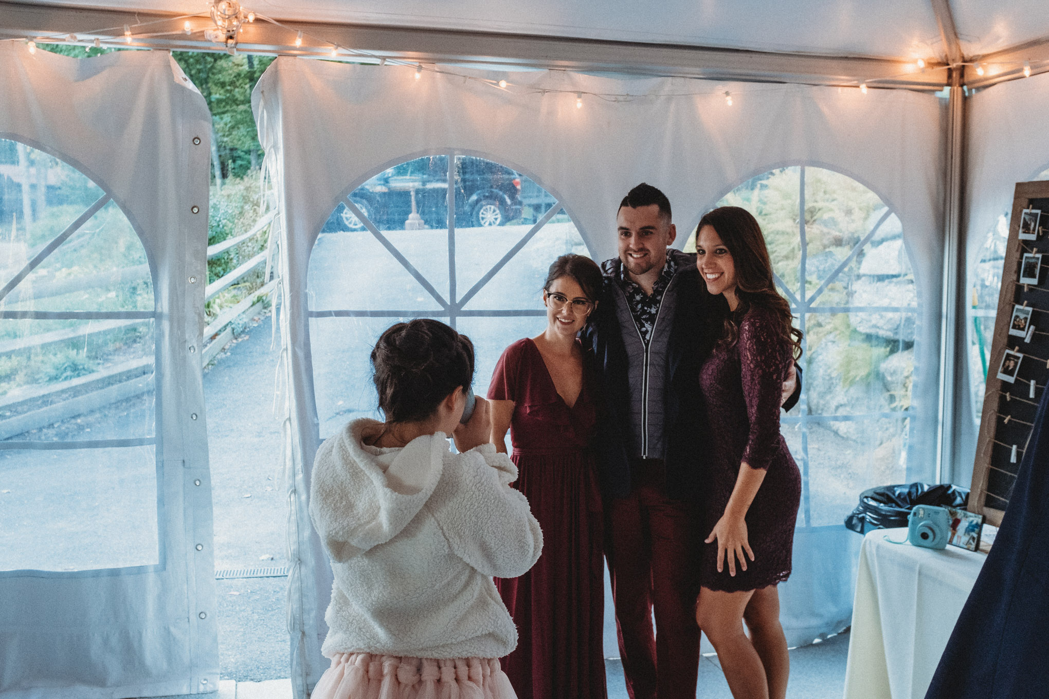 Tracy and Steve Negron pose with friends as their daughter takes a Polaroid photo.