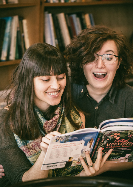Queer androgynous couple reading a book together and laughing.
