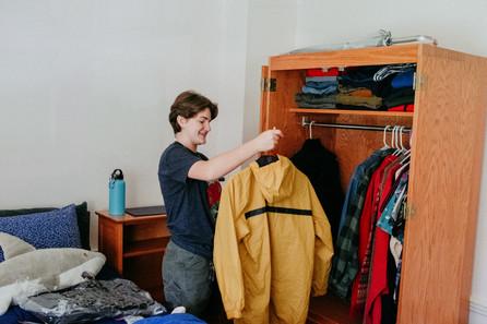 Student hangs yellow rain jacket.