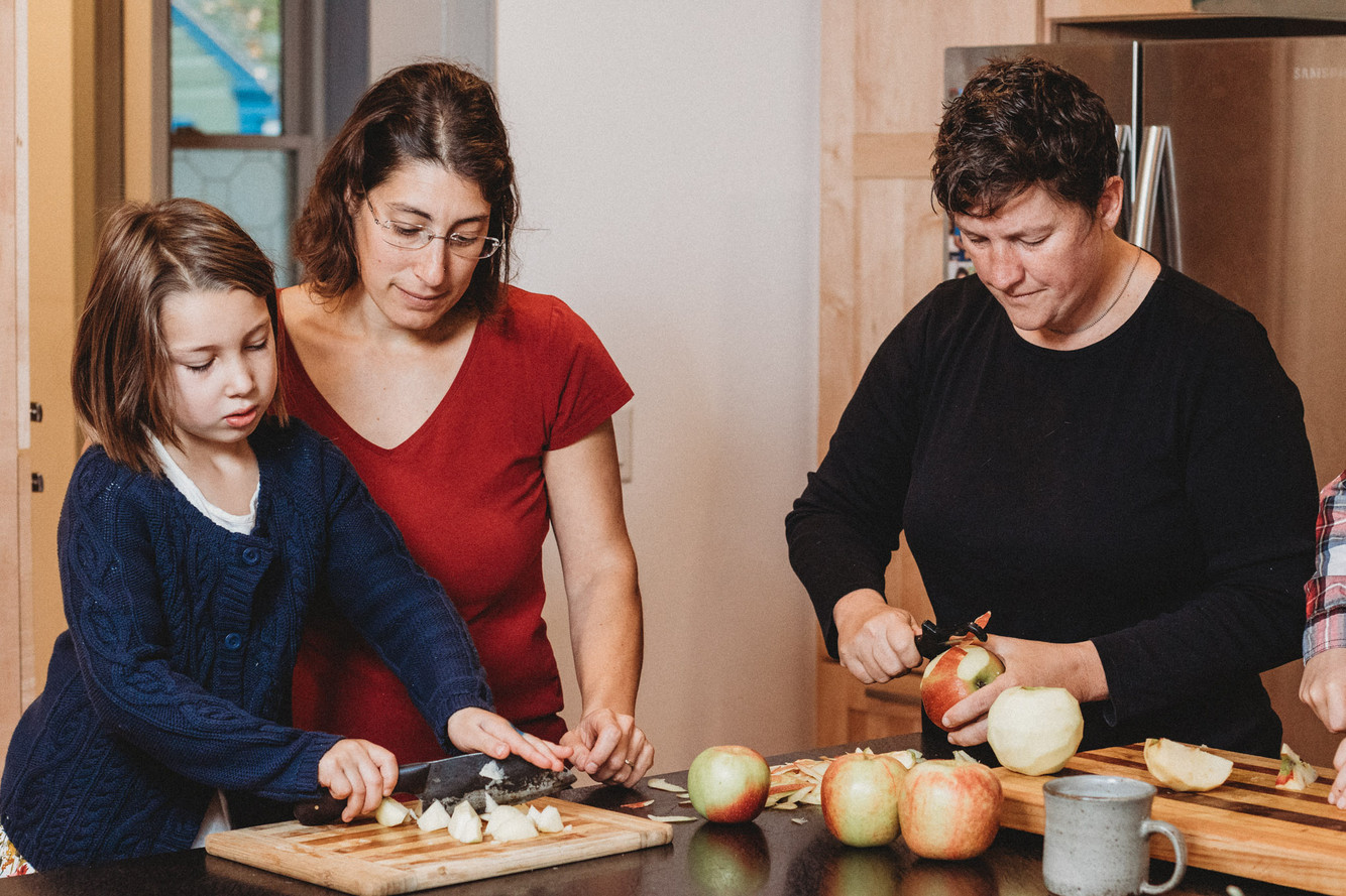 Queer female couple and daughter cook together prepping apple sauce.