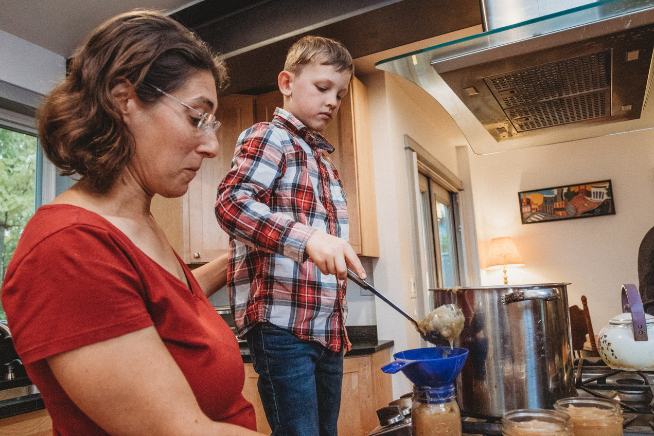 Young boy pours homemade apple sauce into a jar