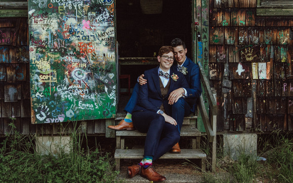 Queer couple sits on the steps of an old, wooden, graffitied art cabin.
