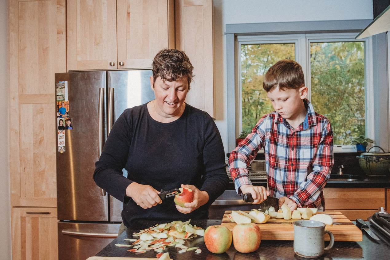 Denise and her son cut apples.