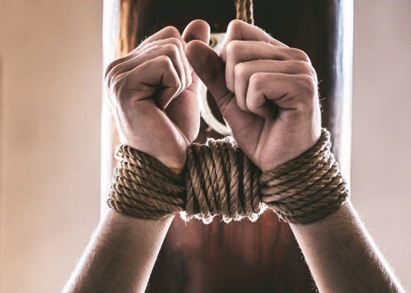 Tied wrists suspended from a post.