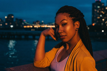 Jazzmine Divinne looking over the NYC skyline at night.