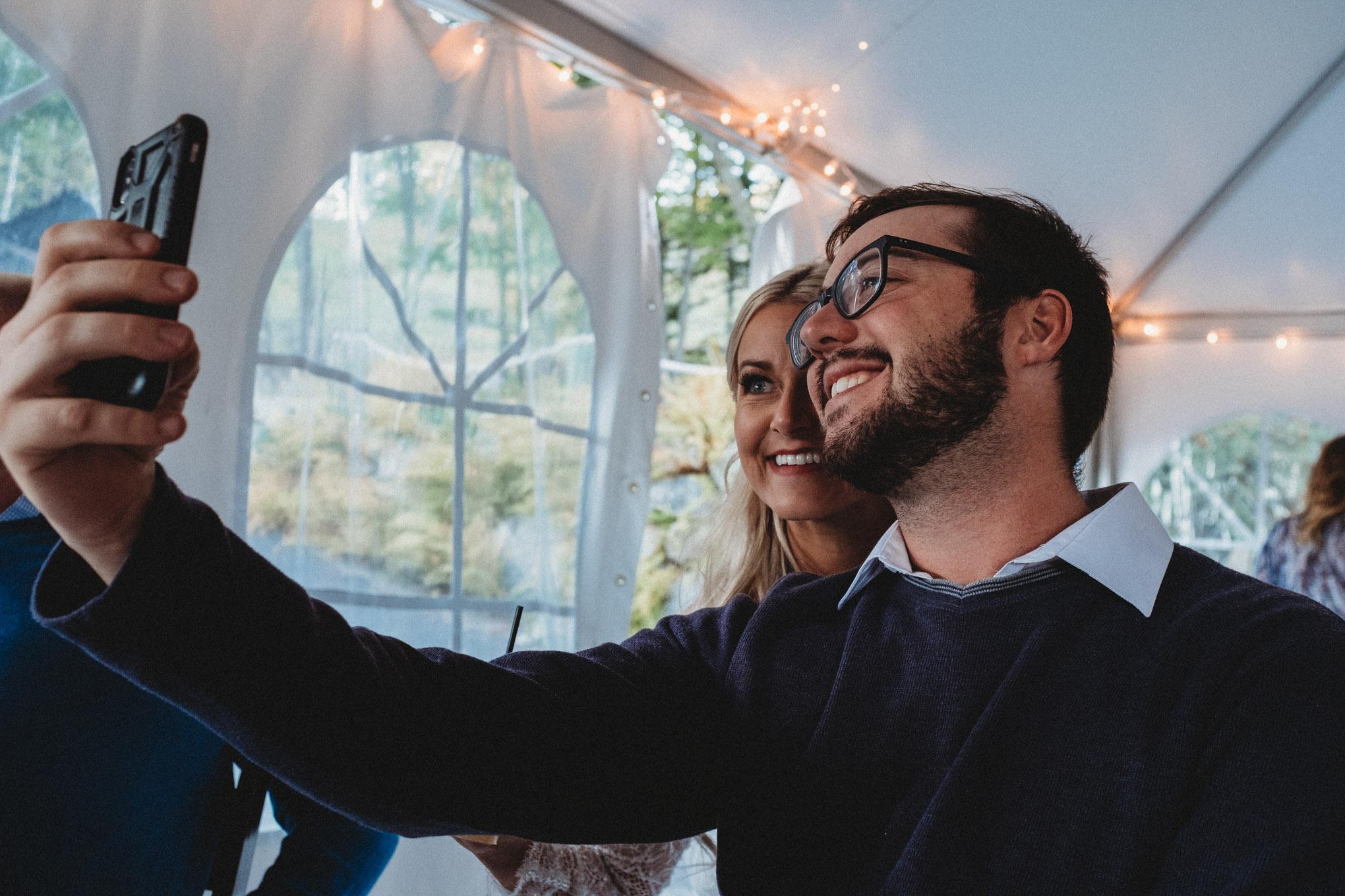 Austin Shea and the bride, Jodi Hogan, smile and take a selfie together.