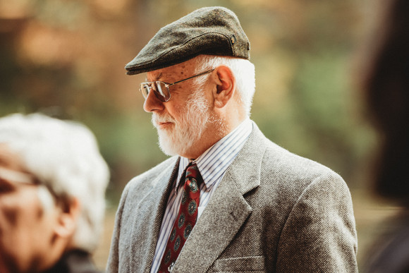 Old man in a suit and cap with a white beard waits for the wedding to start.
