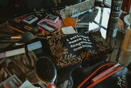 """A table of makeup with a bag that says """"A well-read woman is a dangerous creature."""""""